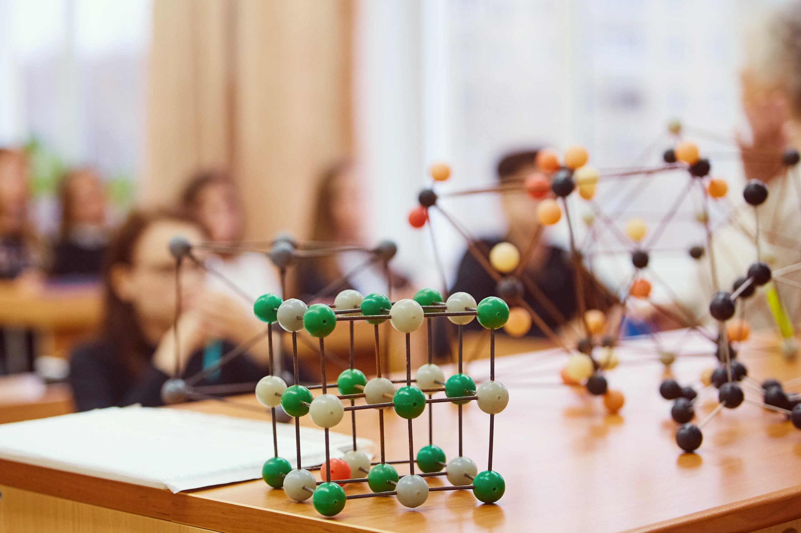 Students sit in the classroom and listen to a lecture in science. Plastic molecular educational model. Soft focus background image