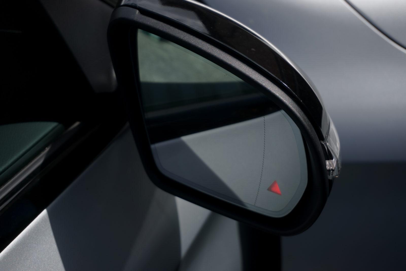 Car door mirror with illuminated blind spot monitoring light warning.