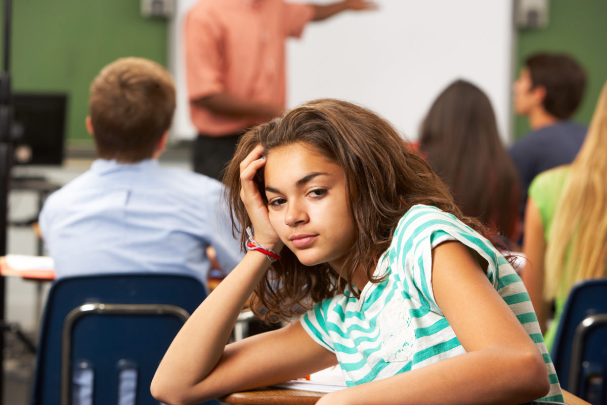 Bored Female Teenage Pupil In Classroom